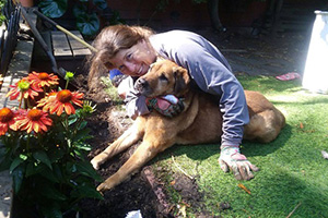Tammy Hilbrich and Spartacus the dog snuggling on a lawn