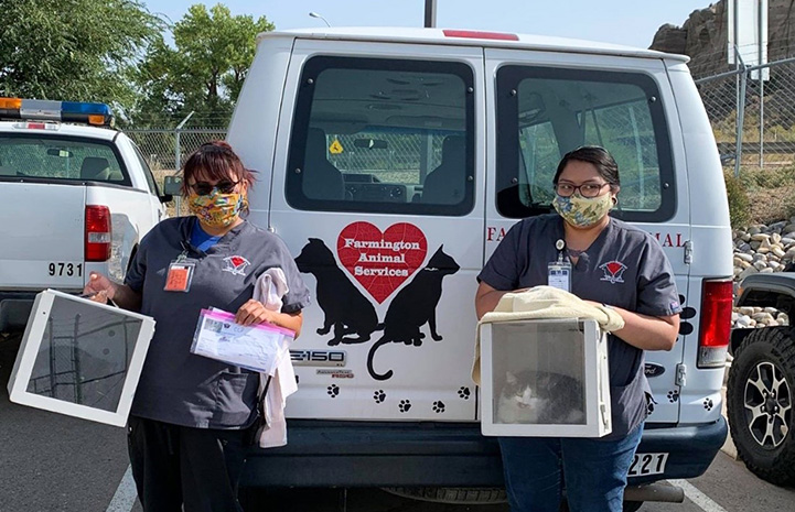 Two masked people wearing Farmington Regional Animal Shelter shirts holding boxes to hold cats, standing at the back of the shelter van