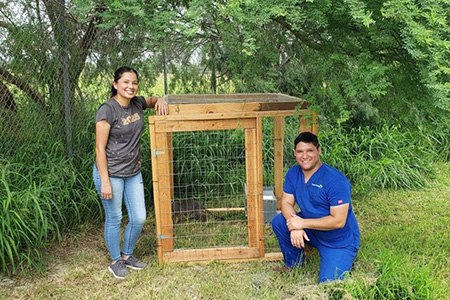 Terri and Jason standing next to a wooden structure designed to acclimate community cats to a new location