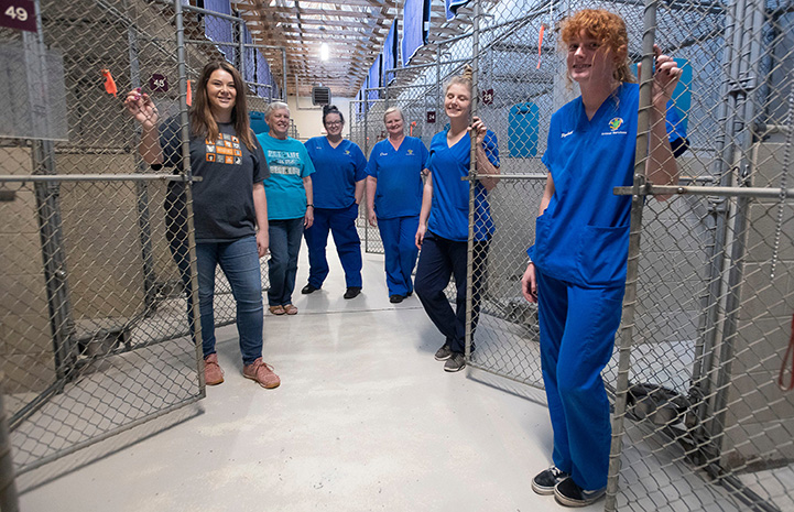 SRCAS staff smiling in front of empty kennels