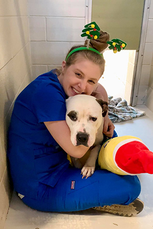 Woman wearing a holiday headband while hugging a dog in a kennel
