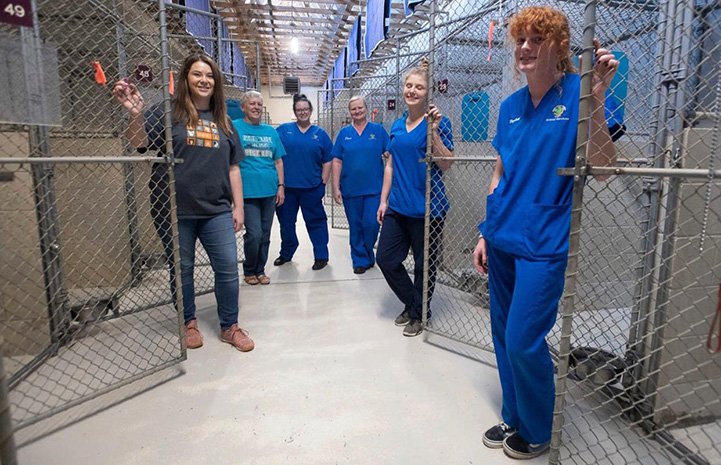 Santa Rosa County Animal Services employees standing outside of empty dog kennels