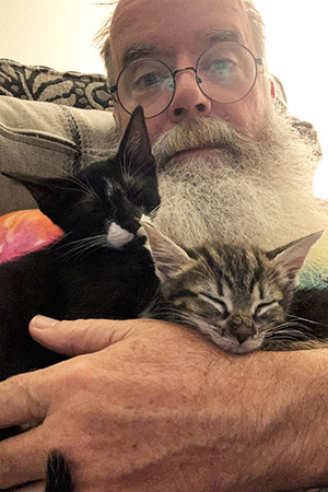 John Tindall cradling a pair of foster kittens in his arms