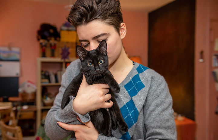 Jelly the black cat being held by a woman