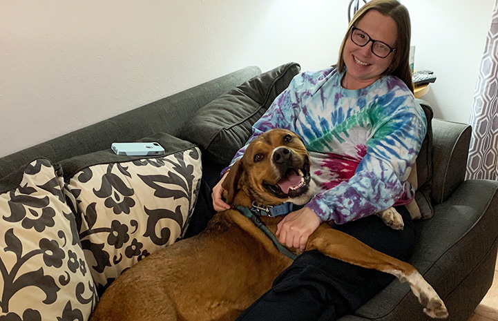 Jess the caregiver lying on a couch with Holy Moly the dog on her lap