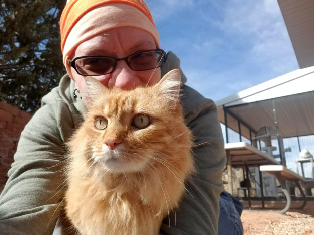 Caregiver Jessica with Hermes the orange longhair tabby cat outside