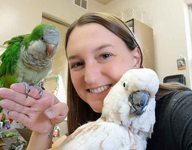 Jessica the caregiver with Rags and Olivet the parrots