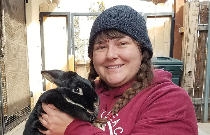 Biff the rabbit being held by caregiver Keala