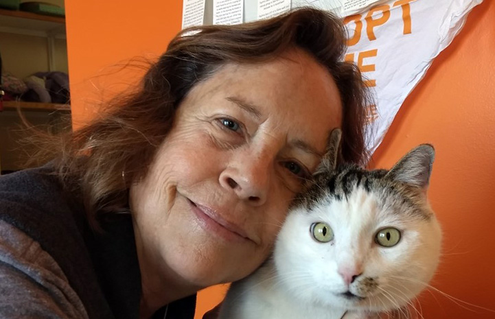 Cat World volunteer coordinator Teresa with her face next to Paytrix the cat