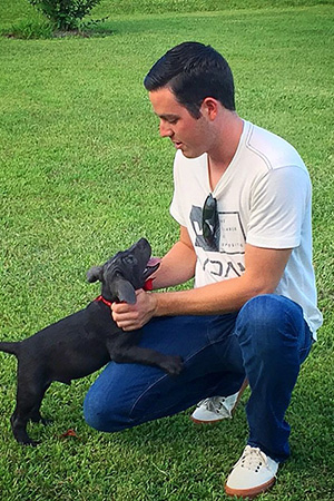 Alex Bowman kneeling in the grass with his dog when a puppy