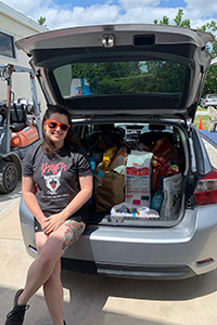 Emily Park sitting on the opened hatchback of a car that stuffed full of pet food donations