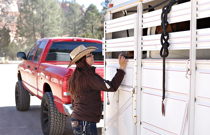 Jessica, wearing a cowboy hat, smiling and putting her hand into the trailer to pet a horse