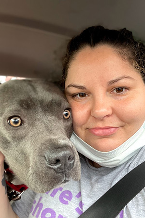 Selfie of a smiling person next to a big, gray dog