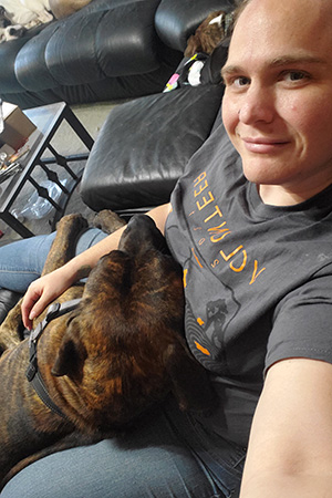 Person sitting down with Ranger the dog lying in the person's lap