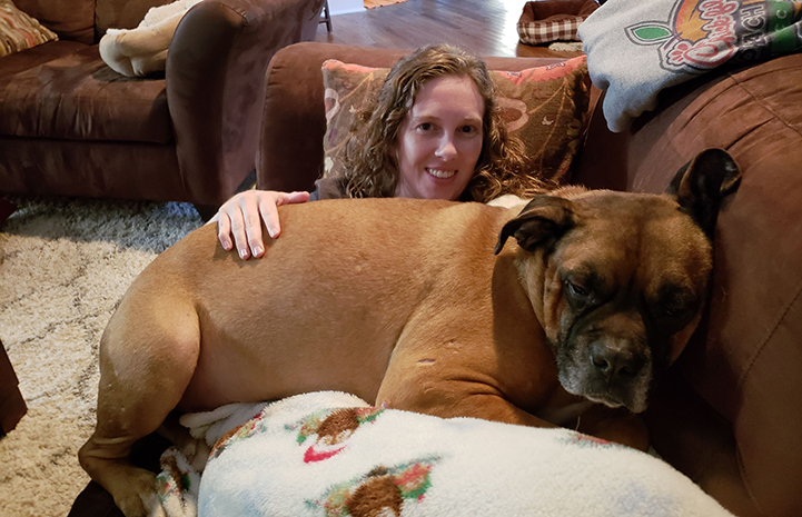 Woman lying on the couch with Beau the foster dog lying on her lap