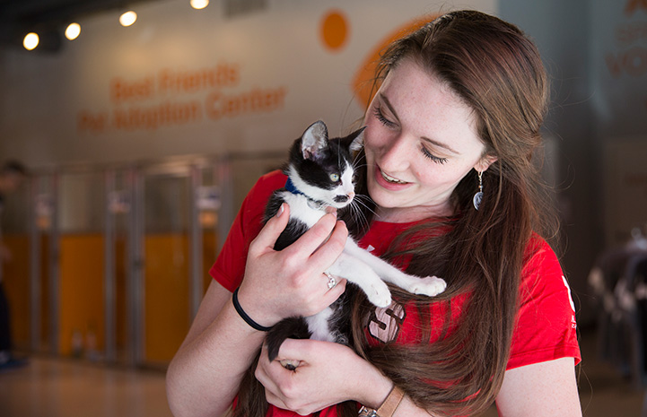 Woman wearing a red T-shirt holding a black and white kitten
