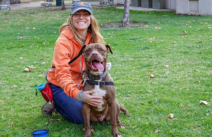 Amber Krzys, smiling and wearing a Best Friends hat, sitting on the grass next to Parker the dog