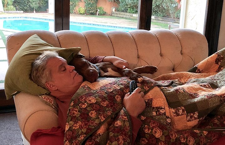 Vince Krzys sleeping with Parker the dog on the couch