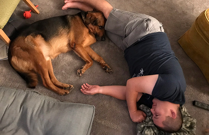 Kenny Nakanishi lying on the floor with Porter the German shepherd snuggled up next to him