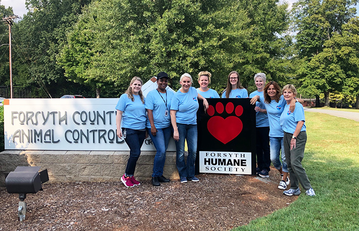 Group of people posing in front of the Forsyth Humane Society sign