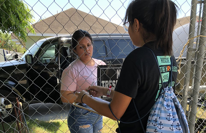 An Action Team member handing literature to another person through a chain-link fence
