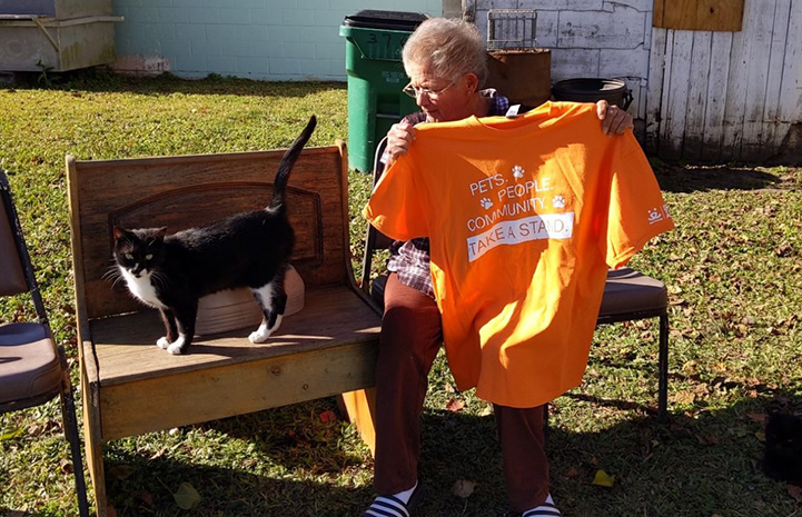 Person sitting down and holding an orange Best Friends Pets People Community Take a Stand T-shirt, next to a black and white cat on a wooden bench