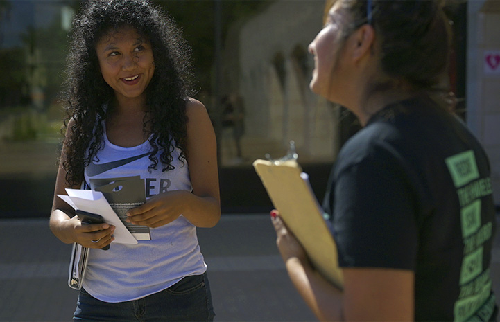 Person holding a clipboard talking to another person smiling and holding paperwork