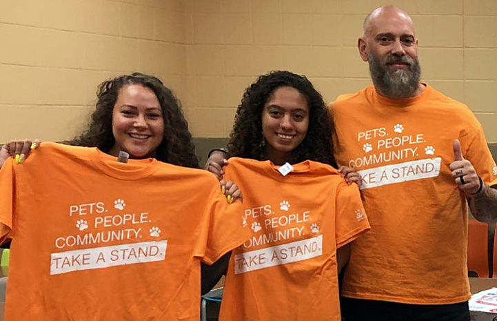 Three people with orange Best Friends Pets People Community Take a Stand T-shirts