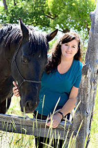 Smiling woman wearing a teal shirt leaning on a fence with a dark brown horse next to her