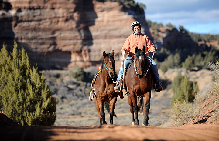Woman wearing a helmet riding a brown horse and leading another brown horse with an orange rock formation behind them