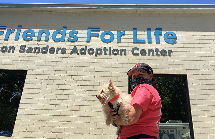 Woman holding a white fluffy dog in front of the sign on the Friends for Life adoption building