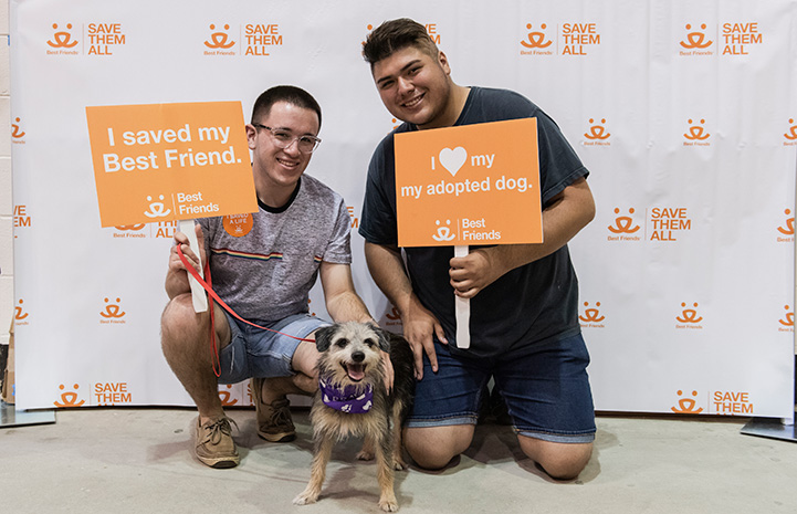 Two young men holding adoption signs in front of a Best Friends backdrop with the dog they'd just adopted at the Houston Super Adoption