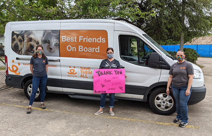 Three masked people standing in front of a Best Friends transport van with a Thank You sign