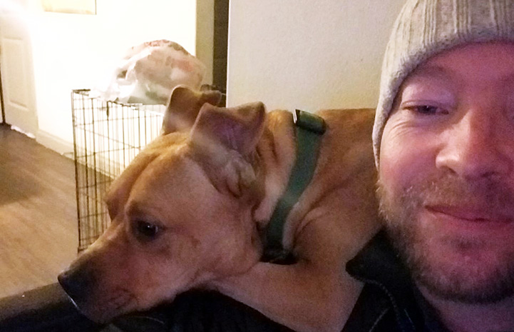 Samwell the dog lying behind a man who is wearing a knit cap's shoulder