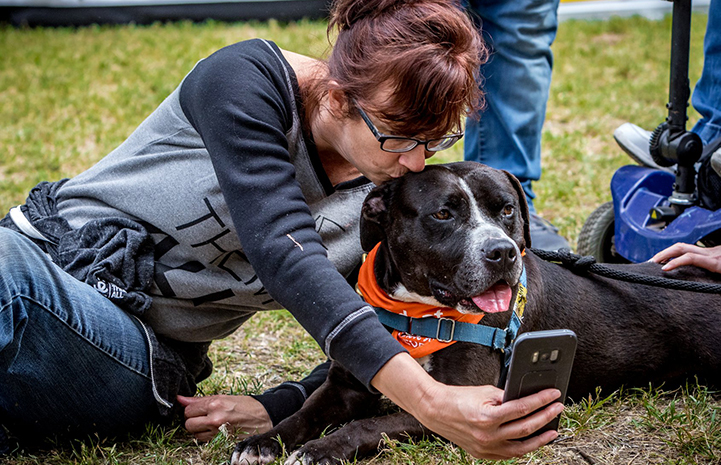 Michelle Sathe taking a selfie with Huck the black and white pit bull terrier