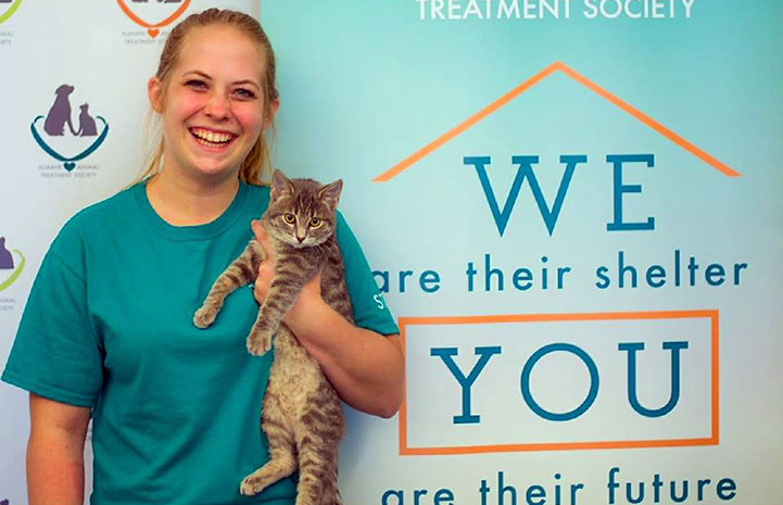 Woman from the Humane Animal Treatment Society holding a gray tabby kitten