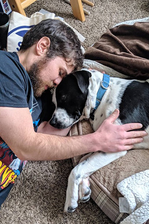 Mulligan, a black and white pit-bull-terrier-type dog, sleeping head-to-head with his adopter Matt