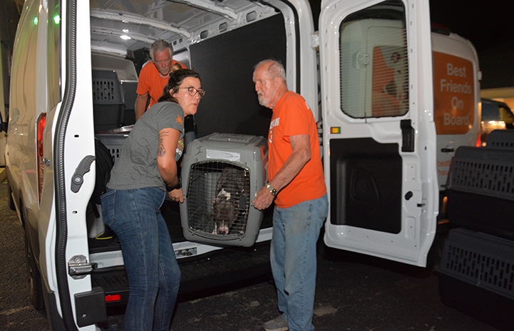 Two people from Best Friends unloading a crate containing a dog from the van to San Antonio