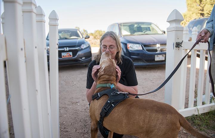 Caroline Lynch bending down to give a hug to DoSiDo the dog