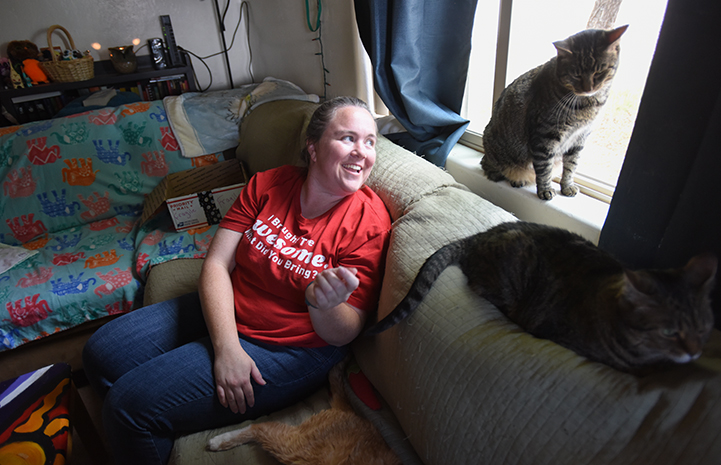 Heather sitting on the couch looking at her two brown tabby cats, RJ and Koda