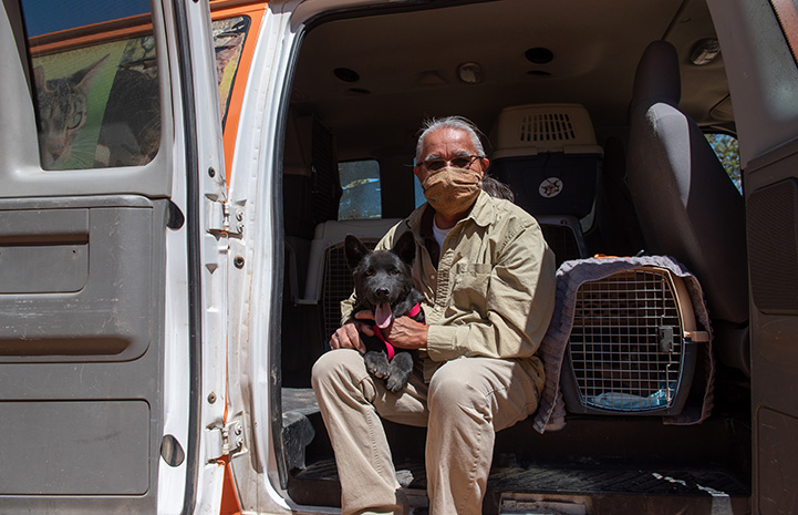 Keith Slim-Tolagai masked and sitting in the back of a van with a black dog and multiple crates