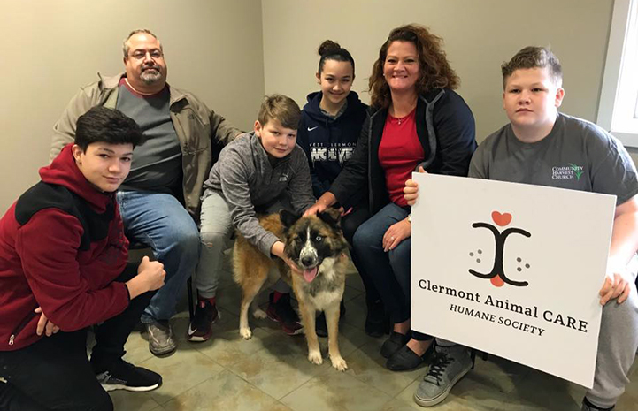 Family posing with an odd-eyed dog while holding a Clermont Animal CARE Humane Society sign