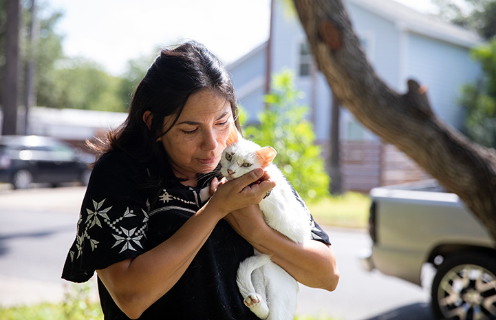 Woman from Palm Valley Animal Society walking outside and holding a white, ear-tipped cat
