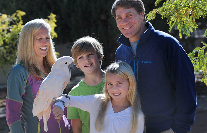 The Scharf family smiling and Berkeley holding a parrot
