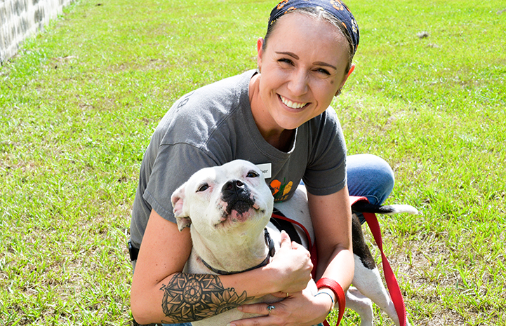 Smiling woman hugging a white pit-bull-type dog