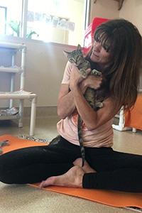 Jennifer Andrews doing yoga while holding a kitten