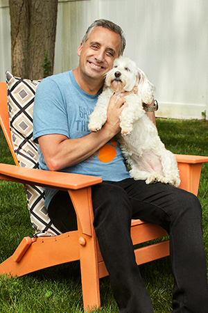 Joe Gatto sitting in a chair and holding a small white dog