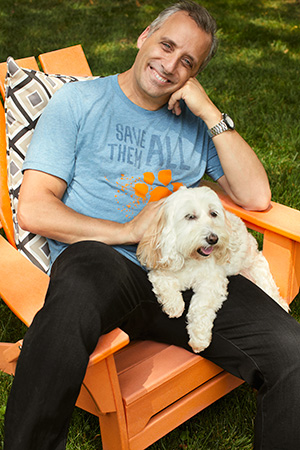 Joe Gatto wearing a Best Friends Save Them All T-shirt and holding a white dog