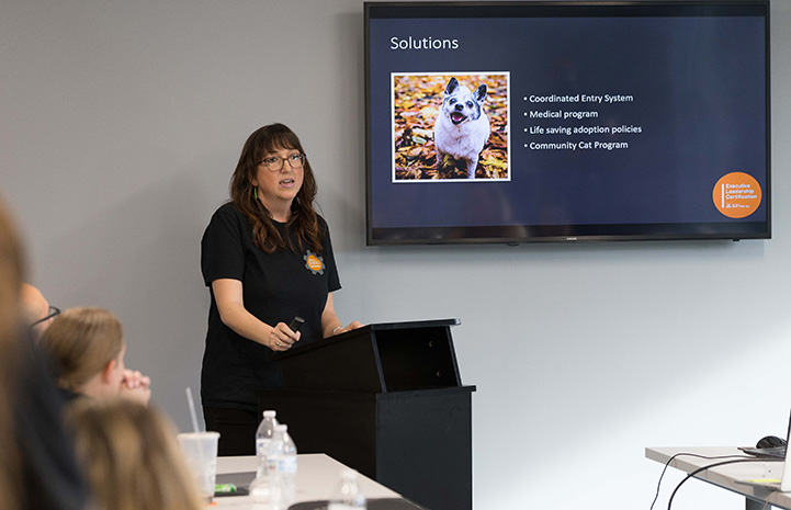 Sarah Hock at a podium addressing a class with a Solutions PowerPoint slide on a screen behind her