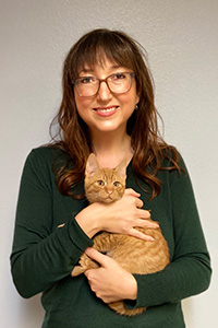 Sarah, Hock, executive director of Joint Animal Services in Washington, holding an orange tabby cat